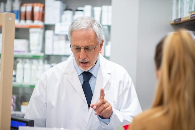 Senior apotheker die een vrouwelijke klant bedient in zijn apotheek