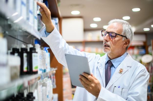 Senior apotheker op zoek naar een product op een plank in zijn winkel en een tablet gebruikt