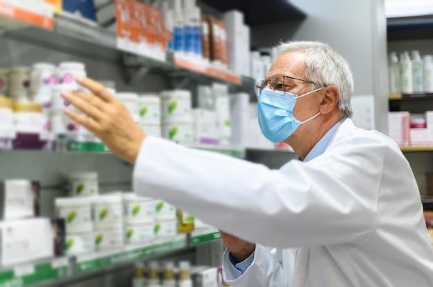 Senior apotheker op zoek naar een product op een plank in zijn winkel, met een masker op vanwege het coronavirus