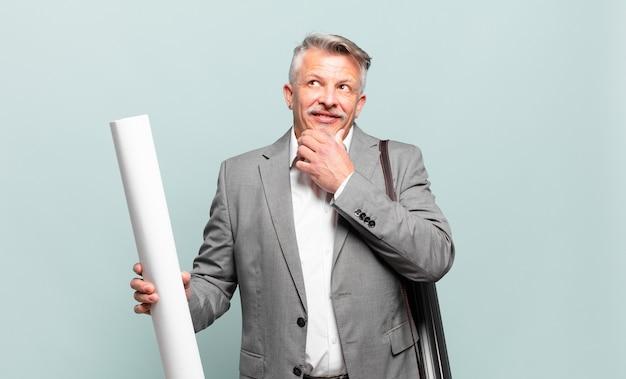 Senior architect die vrolijk lacht en dagdroomt of twijfelt, opzij kijkend