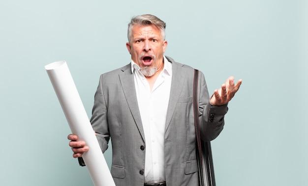 Senior architect voelt zich extreem geschokt en verrast, angstig en in paniek, met een gestresste en geschokte blik