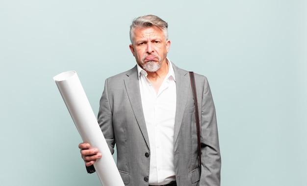 Senior architect voelt zich verdrietig en zeurt met een ongelukkige blik, huilt met een negatieve en gefrustreerde houding