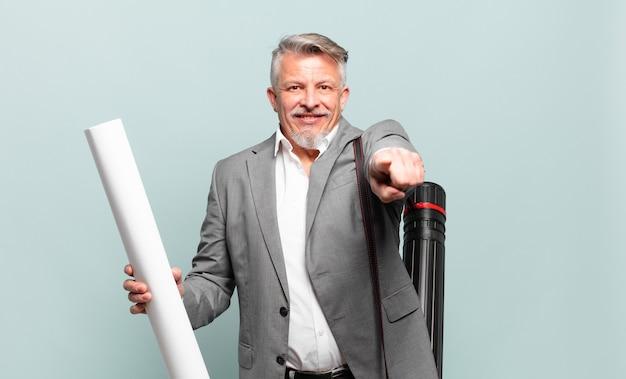 Senior architect wijzend naar voren met een tevreden, zelfverzekerde, vriendelijke glimlach, jou kiezen