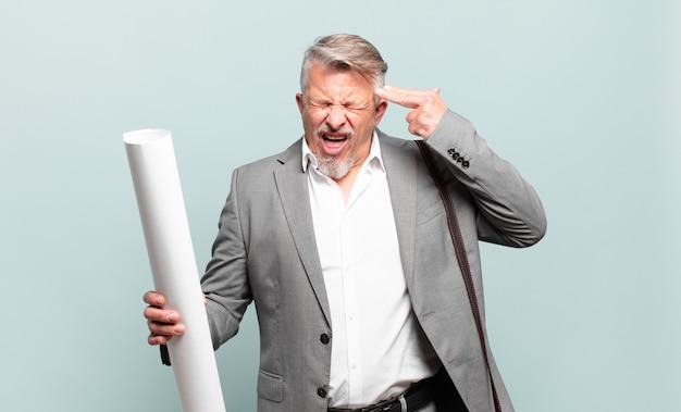 Senior architect ziet er ongelukkig en gestrest uit, zelfmoordgebaar maakt pistoolteken met de hand, wijzend naar hoofd