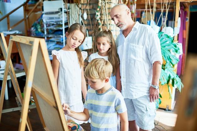 Senior art teacher met groep kinderen in studio