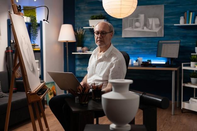 Senior artiest met laptop voor het maken van tekeningen