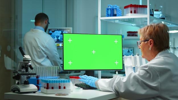Senior arts die 's avonds laat op de computer werkt met een groen scherm in een modern uitgerust laboratorium. team van microbiologen die vaccinonderzoek doen en schrijven op apparaat met chroma key, geïsoleerd, mockup-display.