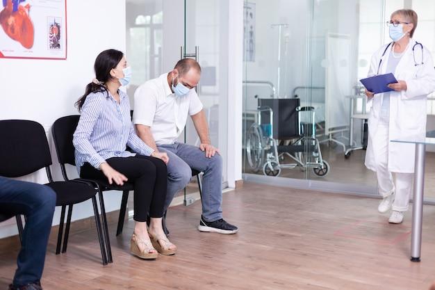 Senior arts die slecht nieuws geeft aan jong stel in de wachtruimte van het ziekenhuis
