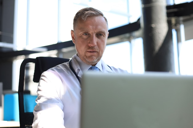 Senior arts in wit gewaad met stethoscoop met behulp van laptop.