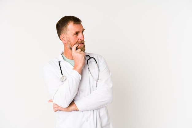 Senior arts man geïsoleerd op witte achtergrond ontspannen denken over iets kijken naar een kopie ruimte.