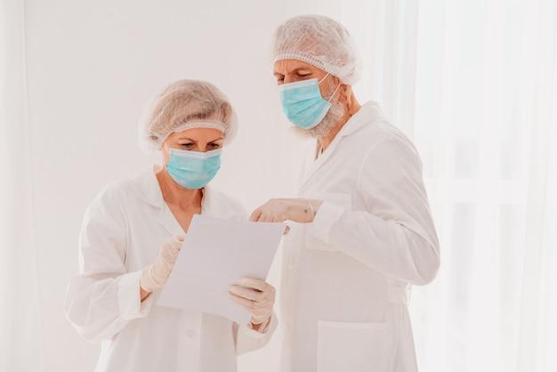 Senior artsen met gezichtsmasker werken samen in ziekenhuis