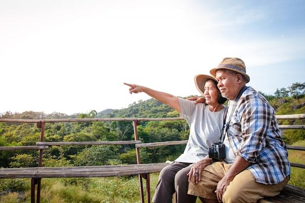 Senior asian couple trekking, reizen, een gelukkig leven leiden met pensioen gezond, kan de frisse natuur zien. concept van gezondheidstoerisme voor ouderen. met kopie ruimte.