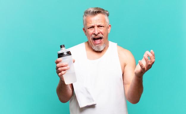 Senior atleet die er wanhopig en gefrustreerd, gestrest, ongelukkig en geïrriteerd uitziet, schreeuwend en schreeuwend