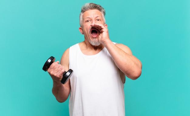 Senior atleet die zich gelukkig, opgewonden en positief voelt, een grote schreeuw geeft met de handen naast de mond, roept