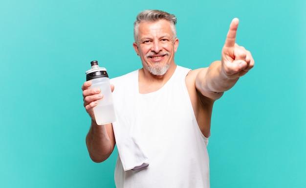 Senior atleet man lacht en ziet er vriendelijk uit, nummer één of eerste met hand naar voren, aftellend