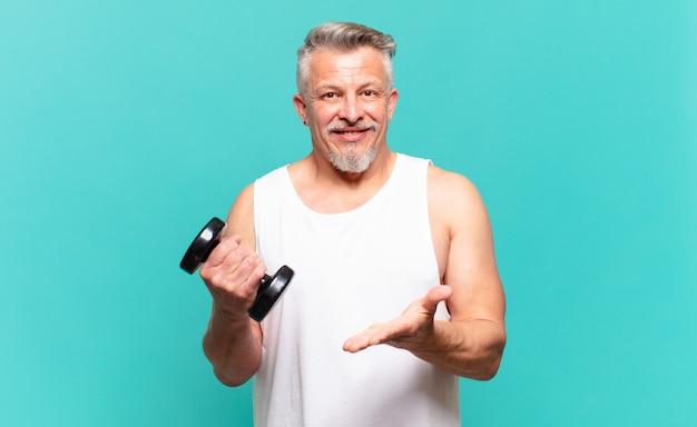 Senior atleet man lacht vrolijk, voelt zich gelukkig en toont een concept in kopieerruimte met palm van hand