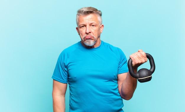 Senior atleet man verdrietig en zeurderig met een ongelukkige blik, huilend met een negatieve en gefrustreerde houding