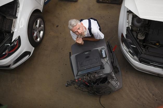 Senior auto-onderhoudsmonteur werkt op de computer in de garage