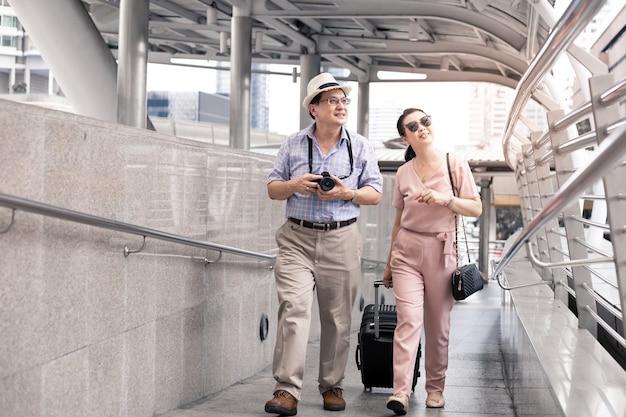Senior aziatisch koppel met een vrouw die een koffer sleept en gelukkig praat met glimlachen op de luchthaven om zich voor te bereiden op reizen. geluk van tantes en ooms in reizen reizen samen met een glimlach.