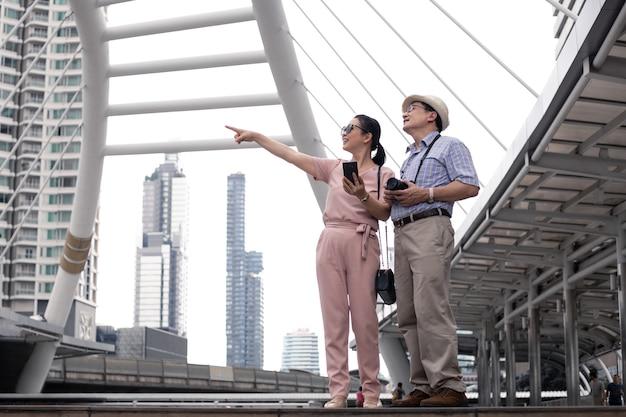 Senior aziatisch stel dat overdag naar interessante plekken in de buitenlucht wijst terwijl ze samen op reis zijn bij een oriëntatiepunt in thailand. senior paar reizen concept.