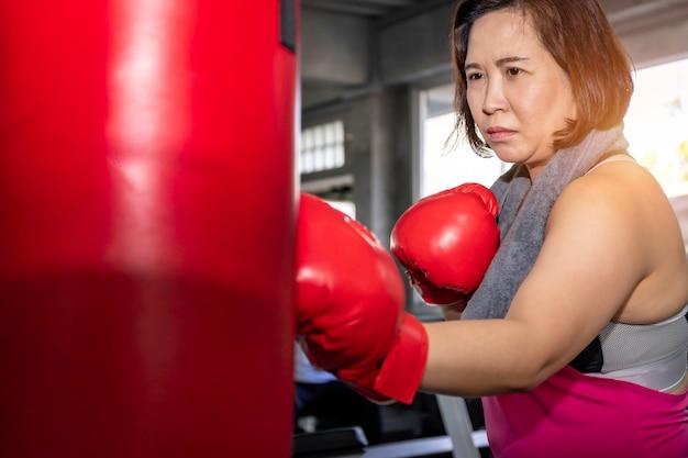 Senior aziatische dikke vrouw training boksen op fitness gym.