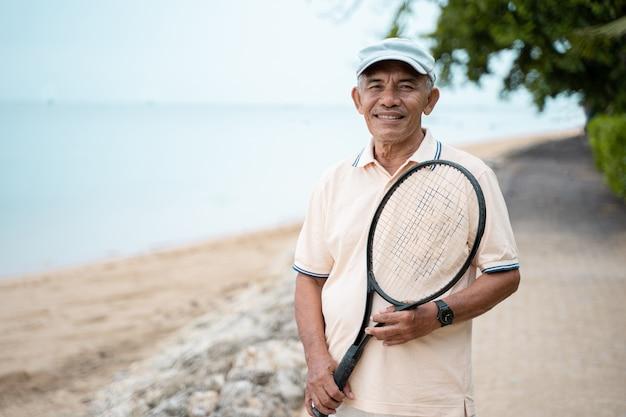 Senior aziatische man die lacht met racket