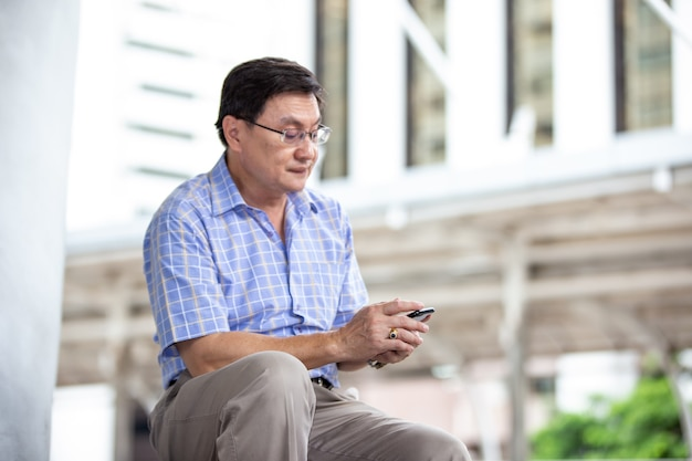 Senior aziatische man die mobiele telefoon gebruikt terwijl hij buiten zit