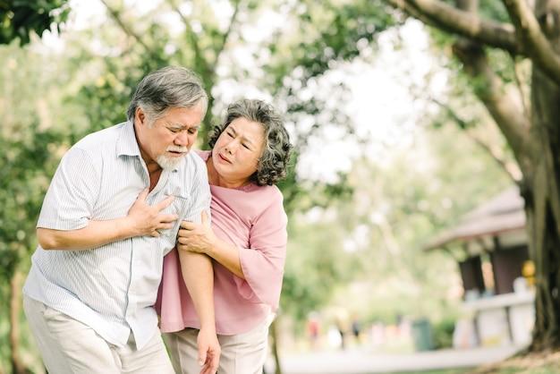 Senior aziatische man die zijn borst vasthoudt en pijn voelt die lijdt aan een hartaanval, terwijl zijn vrouw steun geeft en helpt buiten in het park