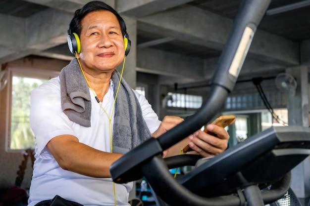 Senior aziatische man in sportkleding luisteren naar muziek en training fietsen cardio op fitness gym.