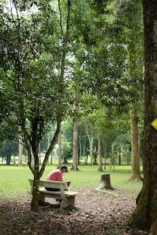 Senior aziatische man met een gezichtsmasker en zittend in een park
