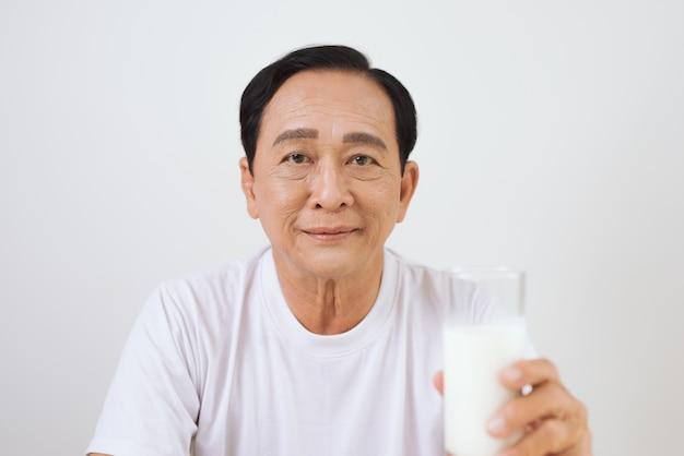 Senior aziatische man met een glas melk