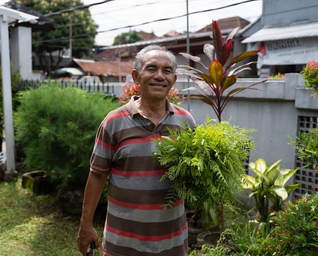 Senior aziatische man met een plant op zijn hand
