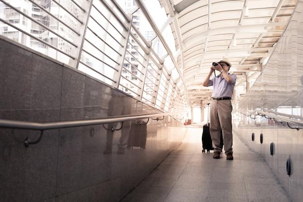 Senior aziatische man sleept bagage en stopt met het maken van foto's op de luchthaven voordat hij vertrekt.