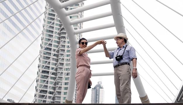 Senior aziatische paar met dans op buiten in reizen gedurende de dag.