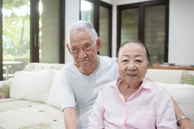 Senior aziatische paar omhelzen elkaar op de bank