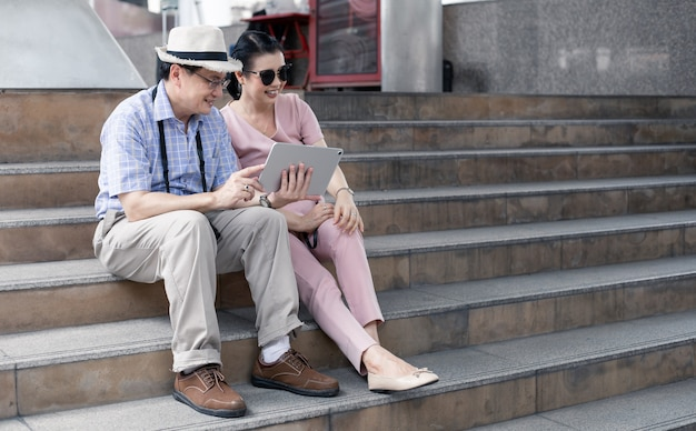 Senior aziatische stellen zitten op trappen, plannen, vinden reisinformatie via tablet met een glimlach. senior paar reizen concept. tante en oom zitten op trappen met een speeltablet tijdens het reizen voor toerisme.