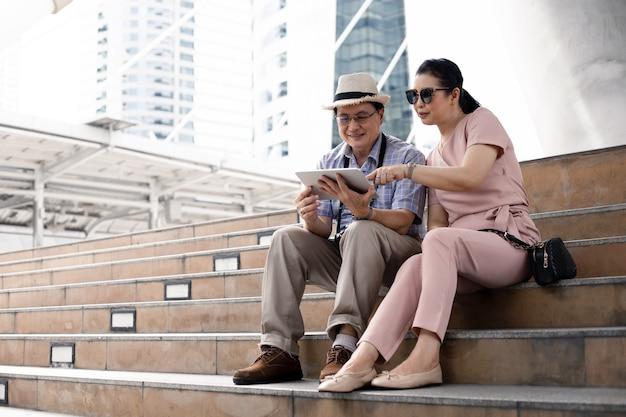 Senior aziatische stellen zitten op trappen, plannen, vinden reisinformatie via tablet.