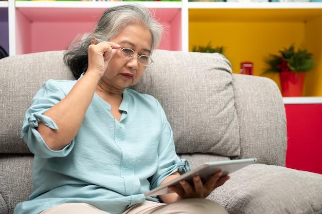 Senior aziatische vrouw die een bril draagt en thuis op een bank ontspant en een tablet gebruikt om nieuws te lezen