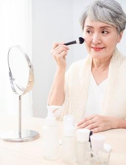 Senior aziatische vrouw die foundation op haar wang aanbrengt met een make-upborstel terwijl ze alleen voor een spiegel zit.