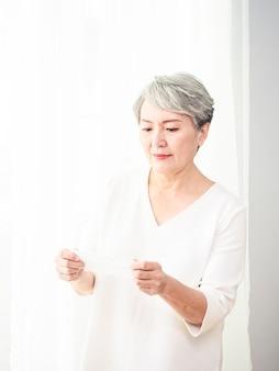 Senior aziatische vrouw die gezichtsmasker draagt tijdens coronavirus en griepuitbraak. virus- en ziektebescherming, thuisquarantaine. covid-19. maskers op- of afdoen.