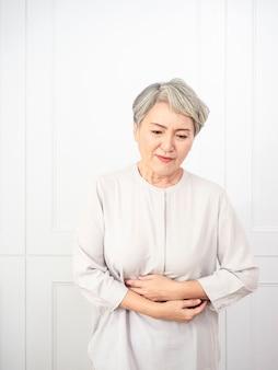Senior aziatische vrouw die vrijetijdskleding draagt met de hand op de buik omdat indigestie, pijnlijke ziekte zich onwel voelt. pijn concept.