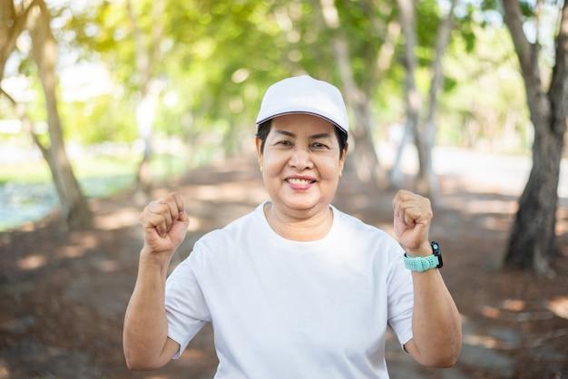 Senior aziatische vrouw handen opgeheven vuisten na pauze training in openbaar park, concept van gezonde oudere vrouw