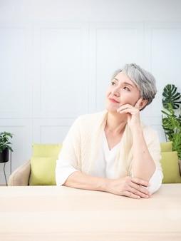 Senior aziatische vrouw met kort grijs kapsel kin bij de hand en zittend aan houten tafel.