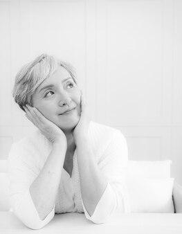 Senior aziatische vrouw met kort grijs kapsel kin op hand in zwart-wit.