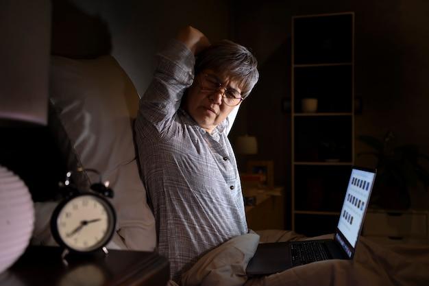 Senior aziatische vrouw met pijnlijke en spierpijn van laptopgebruik in bed