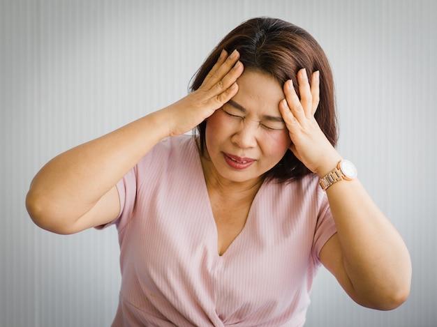 Senior aziatische vrouw van middelbare leeftijd die pijn voelt door plotselinge hoofdpijn en herseninfarcten en houdt haar hoofd vast met een gestrest gezicht. concept van hersen- en hoofdprobleem.