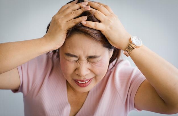 Senior aziatische vrouw van middelbare leeftijd die pijn voelt door plotselinge hoofdpijn en herseninfarcten en houdt haar hoofd vast met een vervormd en kronkelend gezicht. concept van hersen- en hoofdprobleem.