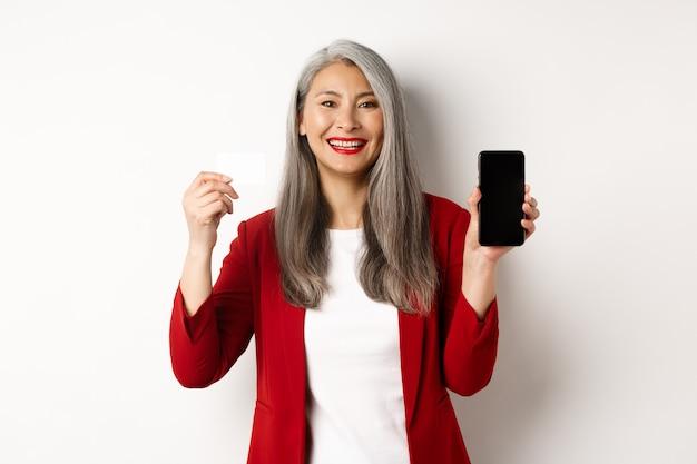 Senior aziatische zakenvrouw weergegeven: plastic creditcard en leeg smartphonescherm, glimlachend in de camera, witte achtergrond.