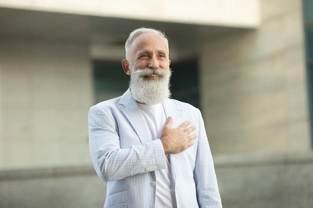 Senior baard man met hand op zijn borst