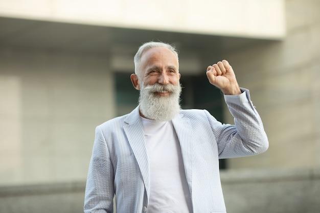 Senior baard man verhogen vuist